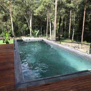 dark green pool interior with black pebblecrete, including decked surrounds