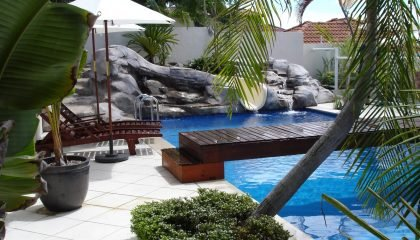 custom designed swimming pool slide incorporate into a rock water feature as part of this very unique pool design.