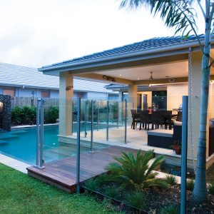 Ultra modern swimming pool design with stone water feature and modern entertainment area