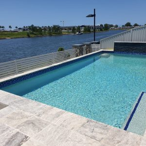 Custom designed swimming pool with tiled surrounds and stack stone water feature overlooking this Gold Coast waterway.