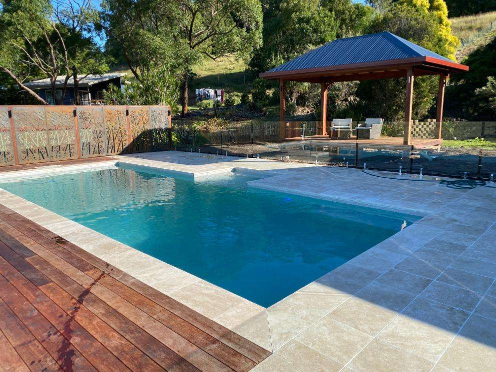 Country side bexhill swimming pool design by Bali Pool Builders. Includes gazibo, travertine tiled and decked pool surrounds.