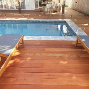 swimming pool with decking, mosaic waterline tiles, and glass fencing