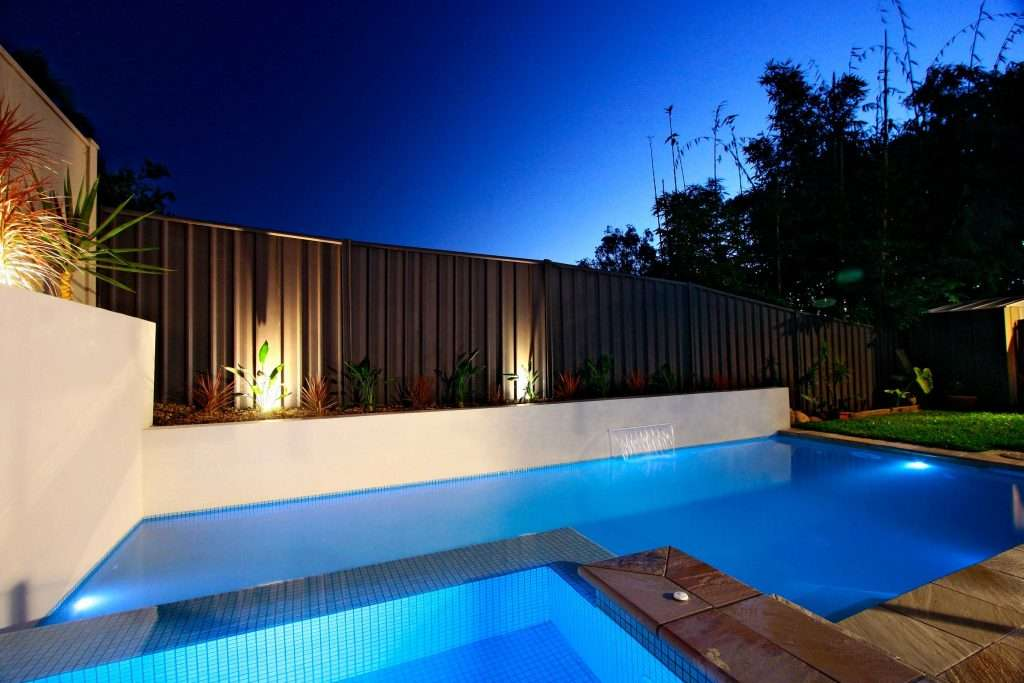 Blue tiles swimming pool and spa combo with rendered retaining walls for the garden, water feature, and simplistic pool surrounds