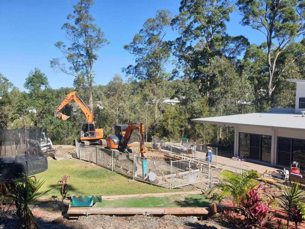 Our team of Gold Coast pool builders quarters of the way through this pool dig as we break through the final rock using the excavator and rockbreaker attachment.