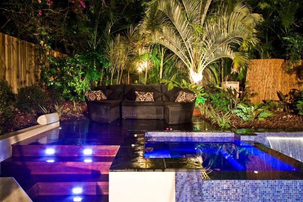 Modern pool and spa combo with water feature and outdoor lounge to relax pool side by the tropical surrounds.