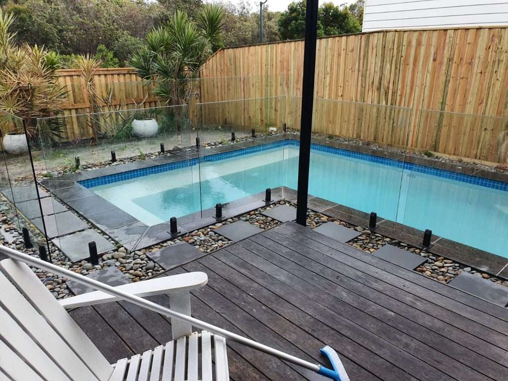 Unique swimming pool design with frameless glass pool fencing, tiled coping, stone surrounds, and decking to match