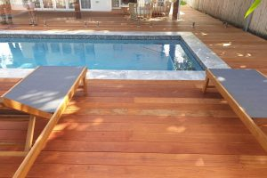 swimming pool with decking, mosaic waterline tiles, timber sun lounges, and glass fencing